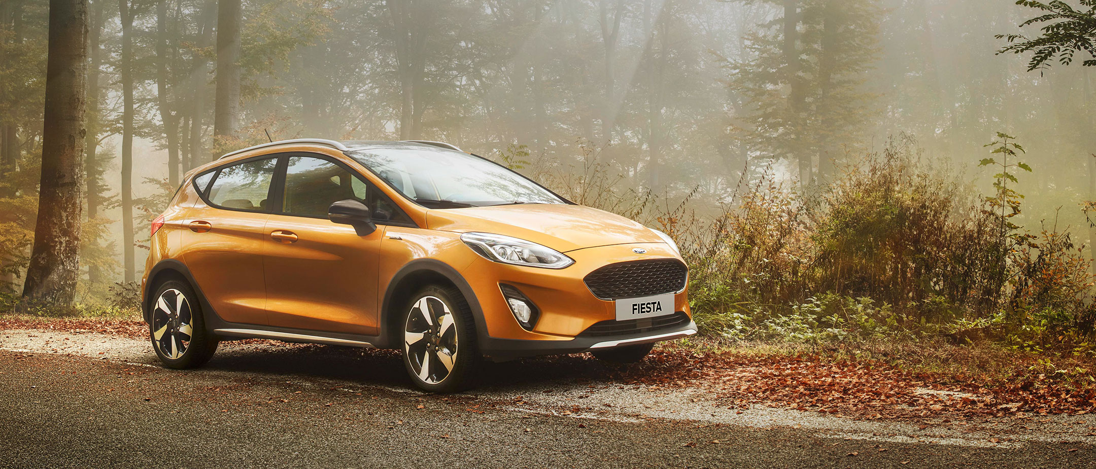 Golden Ford Fiesta Active in the forest side view