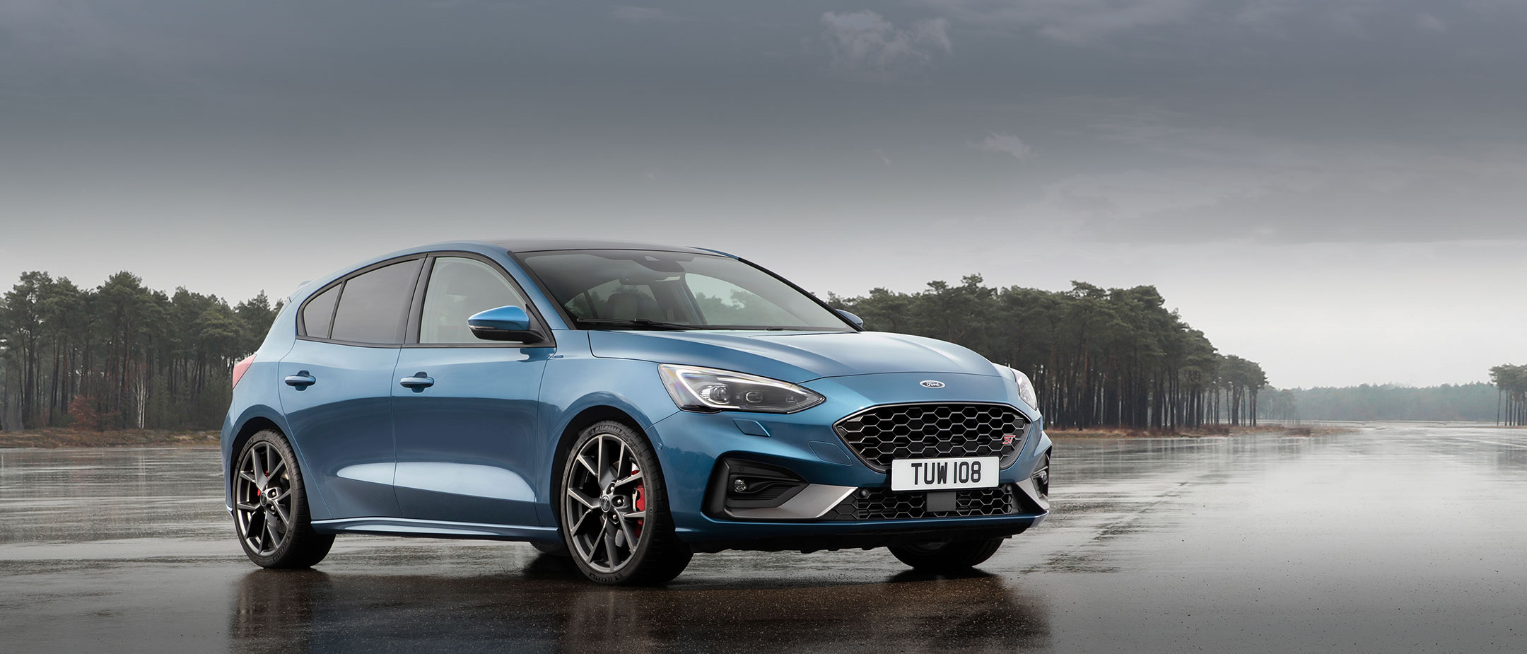 Blue Ford Focus ST parked on wet track