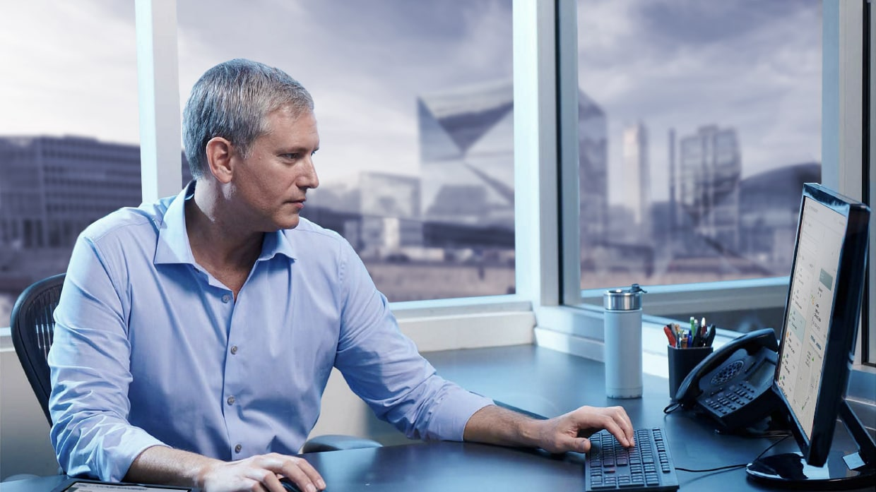 man in office in front of computer